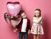Petit garçon offensé avec les ballons de coeur et la petite fille sceptique à la fête d'anniversaire ou à toute autre célébration photo libre de droits