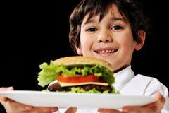 Petit garçon offrant un hamburger de plaque Images stock