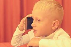 Petit garçon parlant au téléphone exprimant ses émotions Photo stock