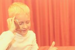 Petit garçon parlant au téléphone exprimant ses émotions Photo libre de droits