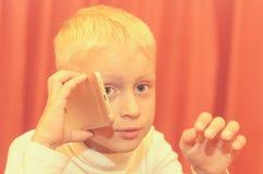 Petit garçon parlant au téléphone exprimant ses émotions Image stock