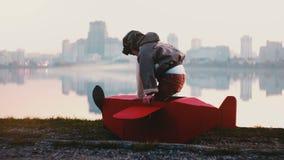 Petit garçon pilote heureux atteignant dans le costume rouge d'avion de carton d'amusement stupéfier le mouvement lent de ville d clips vidéos