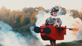 Petit garçon pilote heureux courant le long du lac de coucher du soleil dans le costume plat de carton d'amusement rêvant du mouv banque de vidéos