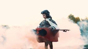 Petit garçon pilote heureux tournant dans le costume d'avion de carton d'amusement avec de la fumée de couleur rouge rêvant du mo banque de vidéos