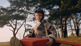 Petit garçon pilote positif sous des arbres dans le costume plat de carton d'amusement portant le mouvement lent rétros d'aviateu banque de vidéos