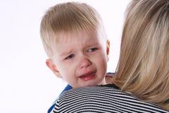 Petit garçon pleurant sur l'épaule de mamans Image stock