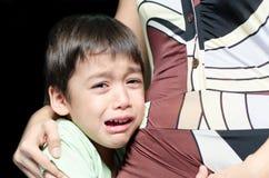 Petit garçon pleurant tenant le sien fond noir de mère images stock