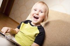 Petit garçon positif avec l'ordinateur de tablette Images libres de droits