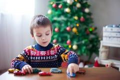 Petit garçon préscolaire adorable, jouant avec des voitures de jouet à la maison dessus Image stock
