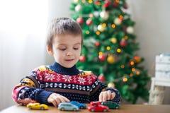 Petit garçon préscolaire adorable, jouant avec des voitures de jouet à la maison dessus Image libre de droits