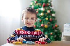 Petit garçon préscolaire adorable, jouant avec des voitures de jouet à la maison dessus Photo stock