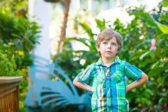 Petit garçon préscolaire blond d'enfant découvrant des fleurs et des papillons au jardin botanique Images libres de droits