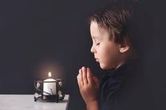 Petit garçon priant, enfant priant, fond d'isolement image libre de droits