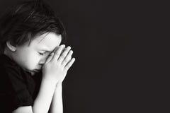 Petit garçon priant, enfant priant, fond d'isolement photos stock