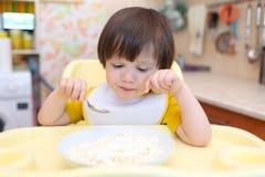 Petit garçon réfléchi mangeant le quark avec la crème sure sur la cuisine Image libre de droits