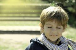 Petit garçon rêvassant ou effectuant un souhait Photographie stock libre de droits