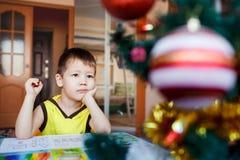 Petit garçon rêveur s'asseyant sur un fond photo stock
