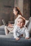 Petit garçon rampant sur le divan tandis que sa mère travaillant sur l'ordinateur portable à la maison Concept de vie de famille image stock