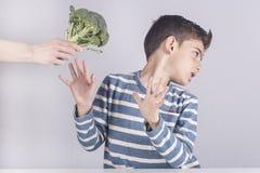 Petit garçon refusant de manger ses légumes photographie stock