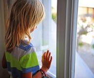 Petit garçon regardant la fenêtre photo libre de droits