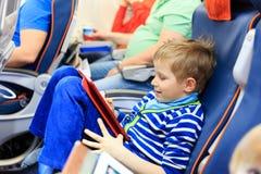 Petit garçon regardant le pavé tactile voyageant en avion Images libres de droits