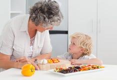 Petit garçon regardant sa cuisson de grand-mère photo stock