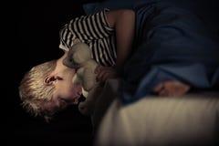 Petit garçon regardant sous son lit photographie stock libre de droits