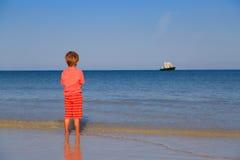 Petit garçon regardant sur le grand bateau la mer Images libres de droits