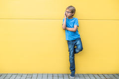 Petit garçon sérieux parlant au téléphone portable se tenant près du mur jaune dehors Photos libres de droits