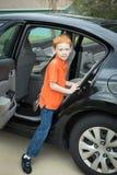 Petit garçon s'élevant dans la banquette arrière d'une voiture garée image stock