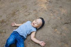 Petit garçon s'étendant sur le sommeil de prétention au sol ou inconscient Photographie stock