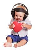 Petit garçon s'asseyant avec des écouteurs, ses mains jugeant le coeur d'isolement Photos stock