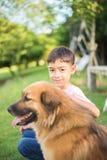 Petit garçon s'asseyant avec l'amitié de chien Photos libres de droits