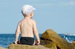 Petit garçon s'asseyant avec le sien de nouveau à une roche sur le bord de la mer dans des troncs de natation, ciel bleu, l'espac Images libres de droits