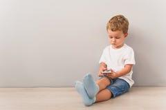 Petit garçon s'asseyant avec le smartphone dans le studio Photographie stock libre de droits