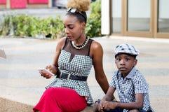 Petit garçon s'asseyant avec sa mère sur une terrasse Images libres de droits