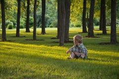 Petit garçon s'asseyant dans l'herbe Photographie stock libre de droits