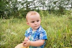 Petit garçon s'asseyant dans l'herbe, coccinelle rampant sur son visage Image libre de droits