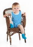 Petit garçon s'asseyant dans la chaise de vannerie Image stock