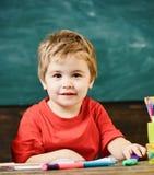 Petit garçon s'asseyant dans la salle de classe Enfant mignon blond tenant le marqueur pourpre photographie stock libre de droits