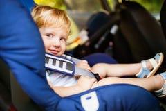 Petit garçon s'asseyant dans le siège de voiture dans la voiture Images stock