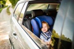 Petit garçon s'asseyant dans le siège de voiture dans la voiture Photos libres de droits