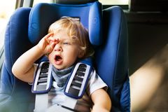 Petit garçon s'asseyant dans le siège de voiture dans la voiture Photos stock