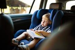 Petit garçon s'asseyant dans le siège de voiture dans la voiture, tenant un livre Images libres de droits