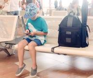 Petit garçon s'asseyant dans un hall de départ d'aéroport Photo libre de droits