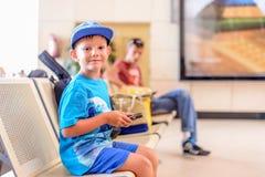 Petit garçon s'asseyant dans un hall de départ d'aéroport Photo stock