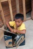 Petit garçon s'asseyant dans une boîte dans le village Photographie stock libre de droits