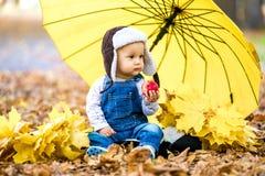 Petit garçon s'asseyant en parc d'automne avec un parapluie et mangeant une pomme photos stock