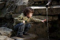 Petit garçon s'asseyant près de la source Photographie stock libre de droits