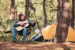 petit garçon s'asseyant près de la tente tandis que père jouant la guitare images stock
